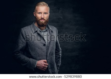 A stylish blond bearded male dressed in elegant, classic jacket.