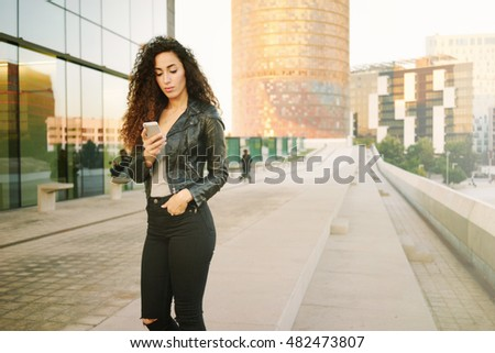 A stylish latin girl in black leather jacket and black jeans is using a smart-phone. Young female with long curly black hairs is looking on a mobile phone screen while standing on a street.