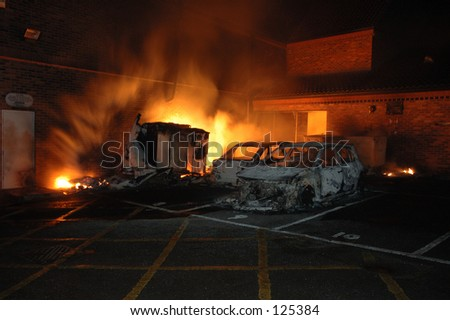 A sub station transformatior burning after it exploded and two nearby cars contaminated