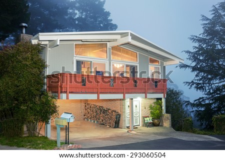 A suburban house with balcony at dusk. Beautifully restored old craftsman style home. - stock photo