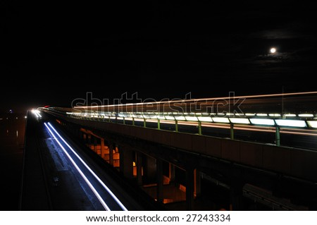 A subway-motor bridge with traces of a train and cars in the moonlit night