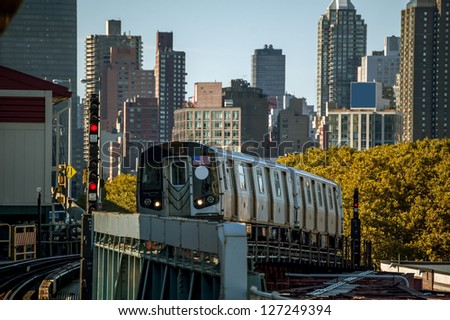 A Subway Train Approaching an Above Ground Station in New York - stock photo