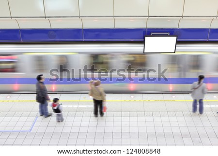 A subway train in motion arriving with moving people at a metro railway station, shot in Taipei, Taiwan, asia - stock photo