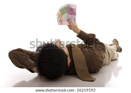 A successful business man lying on the floor looking to euros banknotes