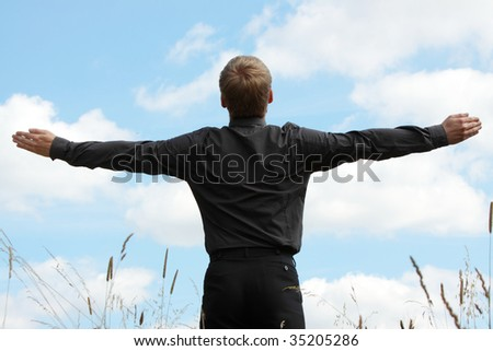 A successful business man with his arm outstretched on a field - stock photo
