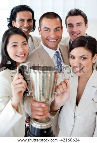 A successful business team holding a trophy. Concept of success.