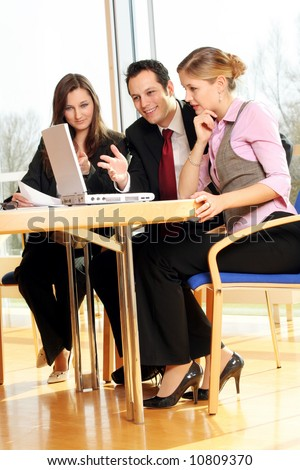 a successful business team is working on a table with documents and a laptop