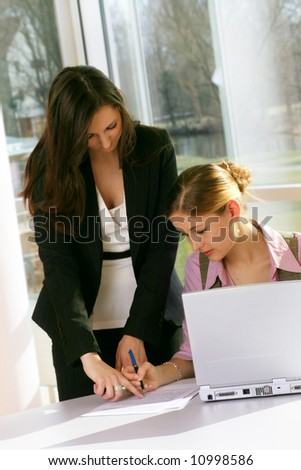 a successful business woman and her secretary with a document on a table with a laptop