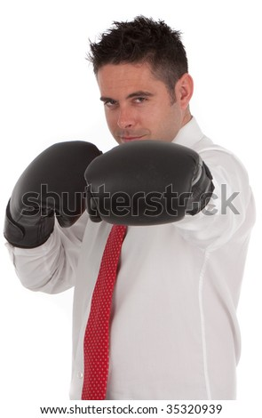 A successful businessman holding boxing gloves up symbolizing conflict or winning a battle wearing a white shirt with a red tie isolated over  white - stock photo