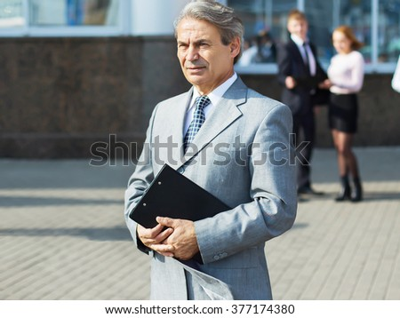 a successful businessman with documents on the background of the - stock photo
