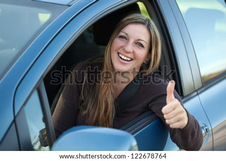 A successful driver is leaning out of the window and showing thumbs up - stock photo