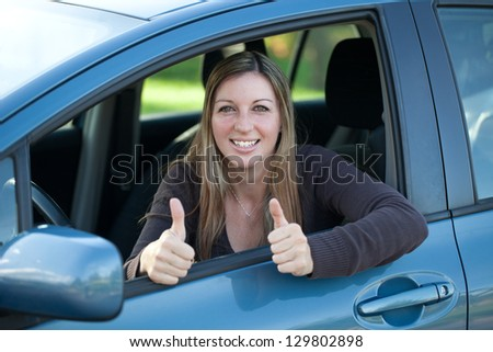A successful driver looking out of the window and showing thumbs up - stock photo