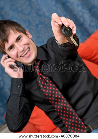 A successful man at home relaxing on the cell phone, offering his car keys to the viewer. - stock photo