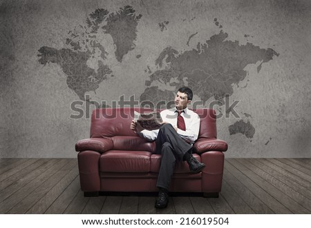 A successful man reads the newspaper, in the background a wall painting showing a globe - stock photo