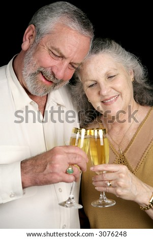 A successful middle aged couple celebrating with glasses of champagne. Isolated on black.