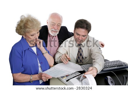 A successful senior couple going over figures with their accountant. - stock photo