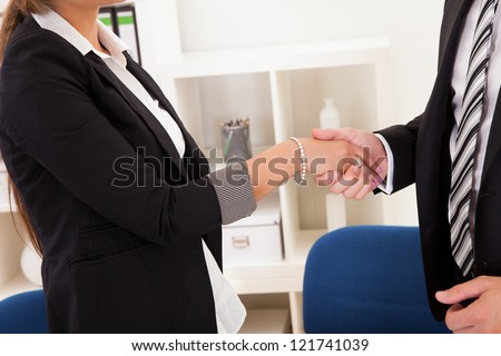 A successful smiling business man and woman stand in an office behind a table shaking hands as they successfully conclude a deal