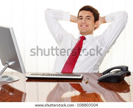 a successful young manager sitting at a desk and smiles. - stock photo