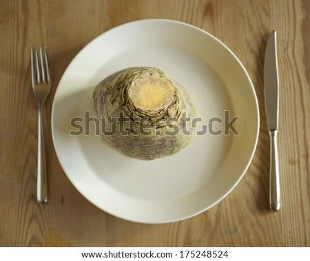A suede on a white plate on a wooden table with cutlery