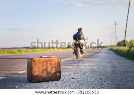 A suitcase on a country road. Couple drive off on the motorcycle leaving the suitcase.