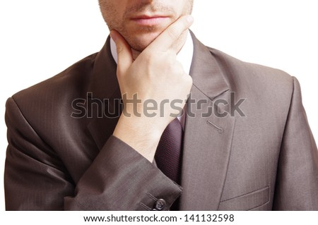 a suited man thinking and holding hand on chin - stock photo