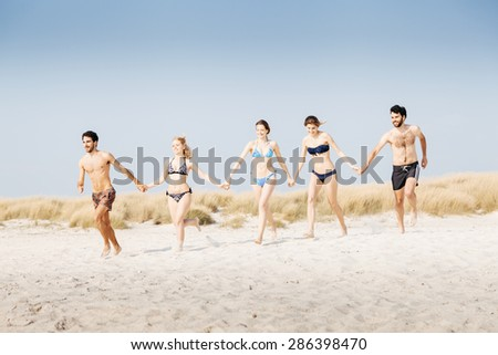 A summer day on a sandy beach, a group of five young people run towards the sea to swim. People are in swimwear on the beach and there are no other people. - stock photo