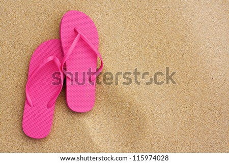 A Summer vacation background with a pair of sandals on beach - stock photo