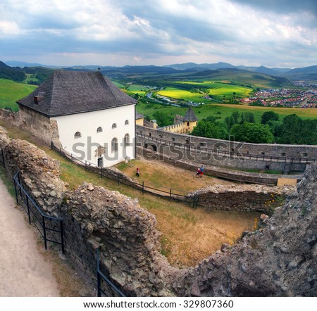 A summertime outlook from the castle of Lubovna, with unrecognizable tourists on the courtyard. This castle is located in Spis region, north-eastern Slovakia.
