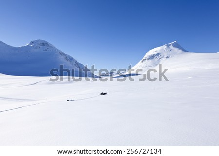 A sunny break from the snowmobile drive in the Scandinavian, Nordic mountains. Trail and valley in the background. Bright sunshine.  - stock photo
