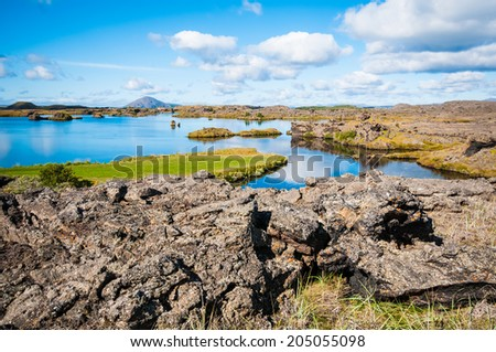 A sunny day on lake Myvatn, Iceland. Clouds reflected in the blue water of a volcanic lake. - stock photo