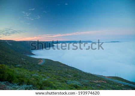 A sunrise landscape with orange clouds on the horizon in the blue sky. In the foreground a green mountain range with a bed of soft white clouds hanging mid air. - stock photo