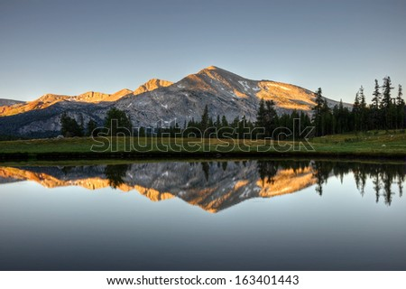 A sunrise reflection of Mammoth Peak and the Kuna Crest on a glacial pond in Dana Meadows, Yosemite National Park, California.