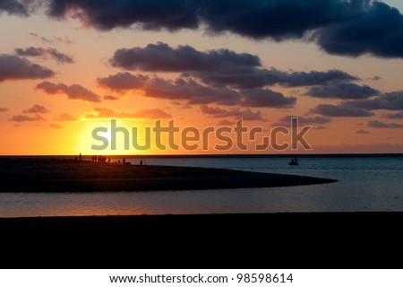 a sunset and fishermen fishing - stock photo