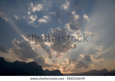 A sunset appears to be streaming its rays from a mountain peak in Banff National Park, Alberta, Canada. - stock photo
