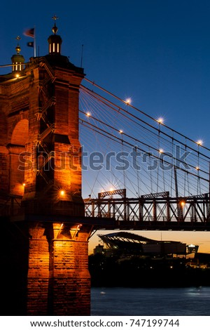 A sunset / blue hour view of the historic Roebling wire suspension bridge that crosses the Ohio River between Cincinnati, Ohio and Covington, Kentucky.