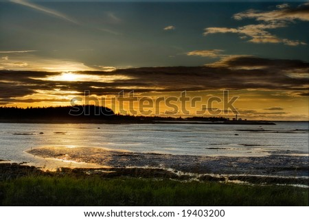 A sunset over the bay and a lighthouse - stock photo