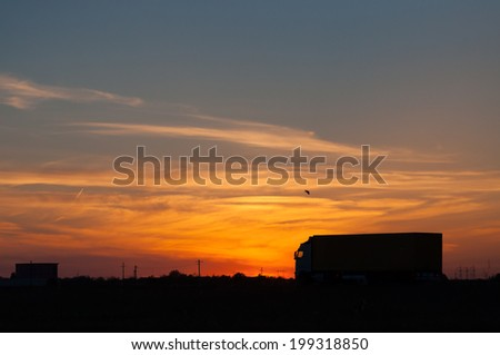 A sunset view and a truck passing on the highway - stock photo