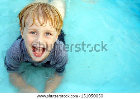 A super happy child is laying in a small wading pool, looking up at the camera and smiling.  Empty space off to the side for text / copy space.