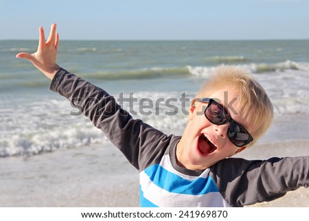 A super happy young child is smiling with joy with his arms raised up while standing on the white sand beach by the ocean on summer vacation. - stock photo