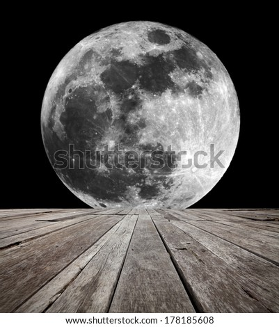 A supermoon on a clear night in the horizon of an empty timber deck platform. Element of this image furnished by NASA. - stock photo