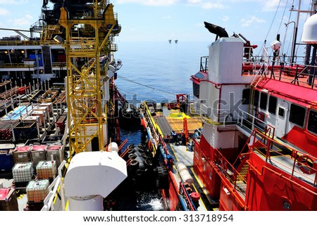 A supply boat docking at an offshore barge platform - stock photo