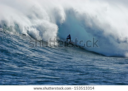 A surfer about to be enveloped by a huge foam ball. - stock photo