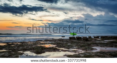 A surfer coming out of raging sea to the shore. A beautiful sunset in the evening. - stock photo