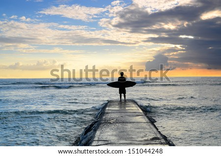 A surfer enjoys the view of the sunset on a jetty after a day of surfing. - stock photo