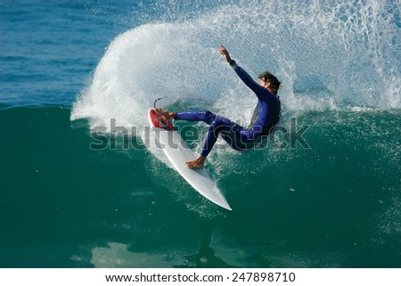 A surfer executes a radical cutback on a beautiful, blue wave in the ocean. - stock photo