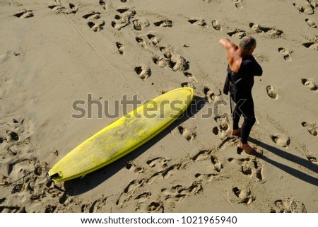 A surfer gets ready to go surfing during the  morning