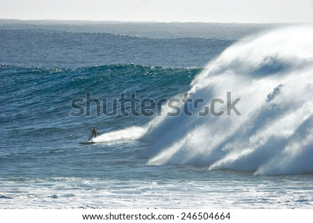 A surfer glides across the face of a huge wave.