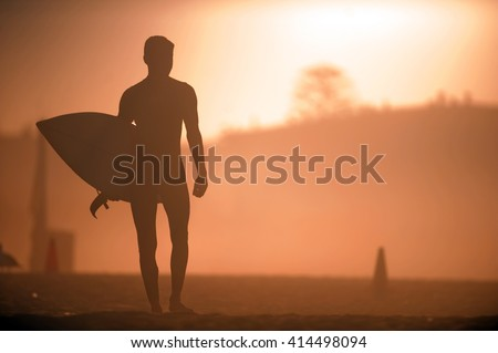A surfer grabs his board and evaluates the waves at sunrise. - stock photo