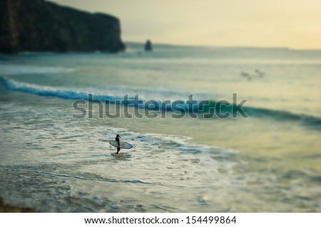 A surfer in the sea - stock photo