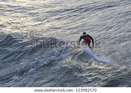 A surfer rides a big wave from Hurricane Sandy as seen from behind, Folly beach, South Carolina, USA, on October 25, 2012 - stock photo